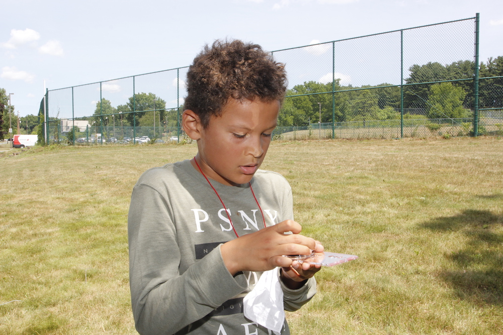 A young boy consults a compass outside on the HCC campus