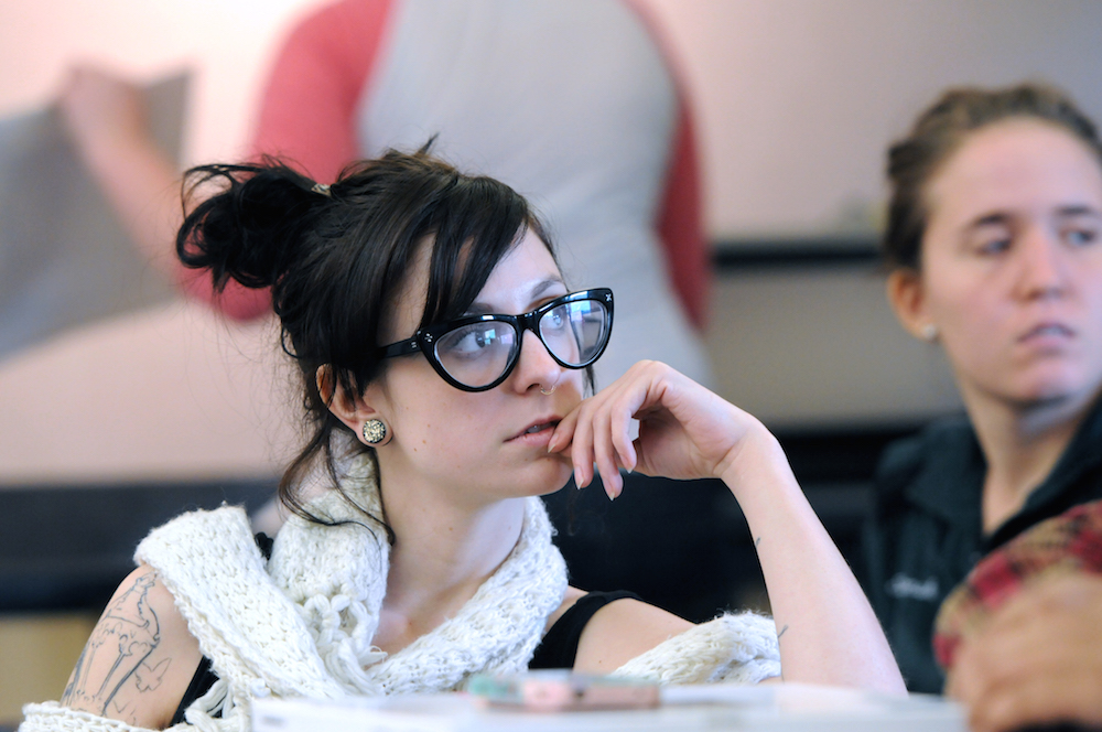 A female student wearing glasses in class
