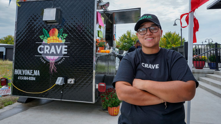 A color photo of HCC alumna Nicole Ortiz next to her food truck