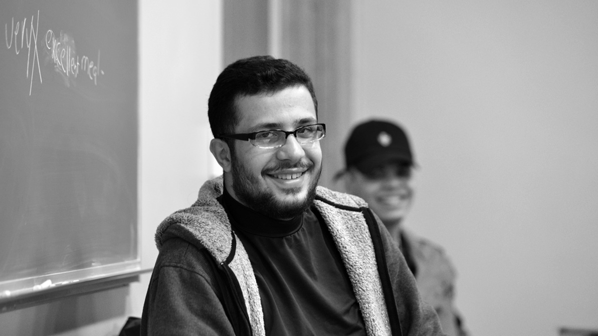 A black-and-white photo of a smiling male student