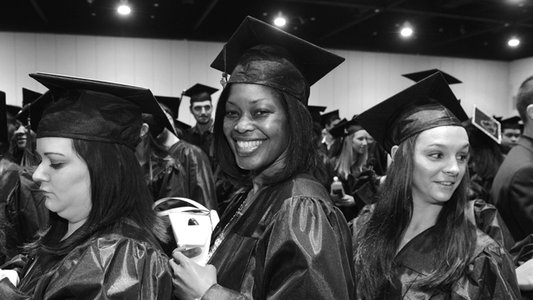 A black-and-white photo of a smiling female student wearing a graduation cap