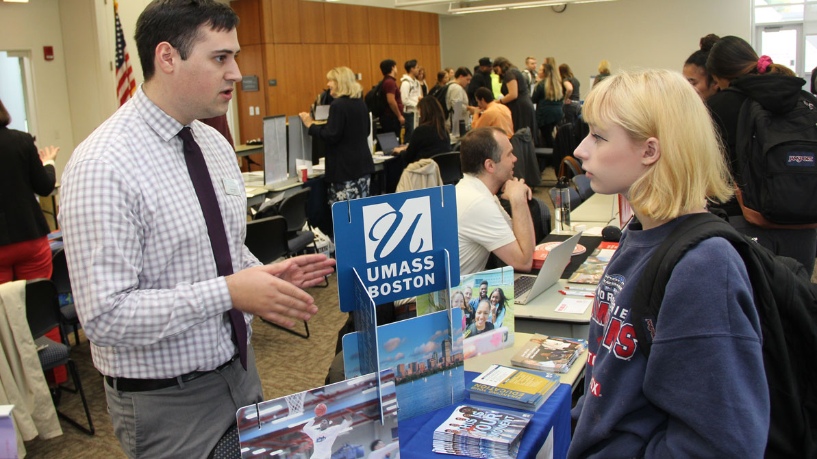 A female student talks to a representative from UMass Boston at HCC's annual transfer fair.