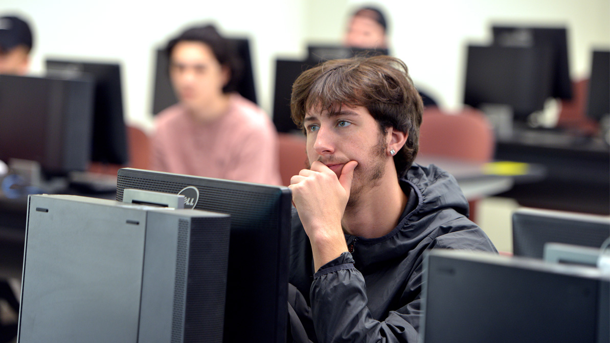 A male student working in a computer lab