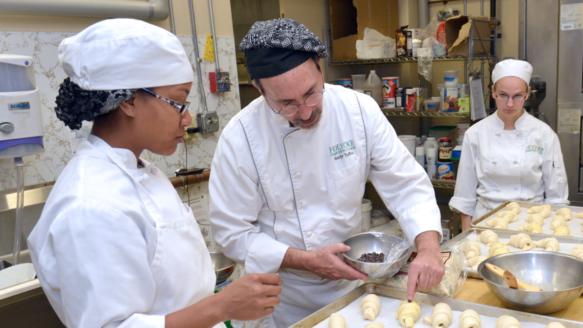 A culinary teacher works with two students in the kitchen
