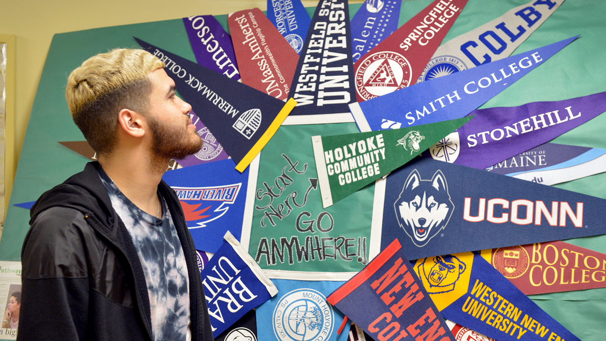 A male student looks at a bulletin board display made up of pennant flags from a variety of four-year schools and universities