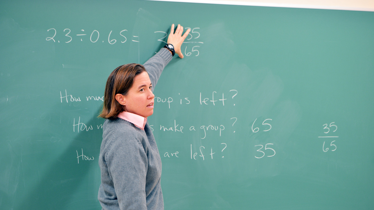 A female instructor gestures to a chalkboard