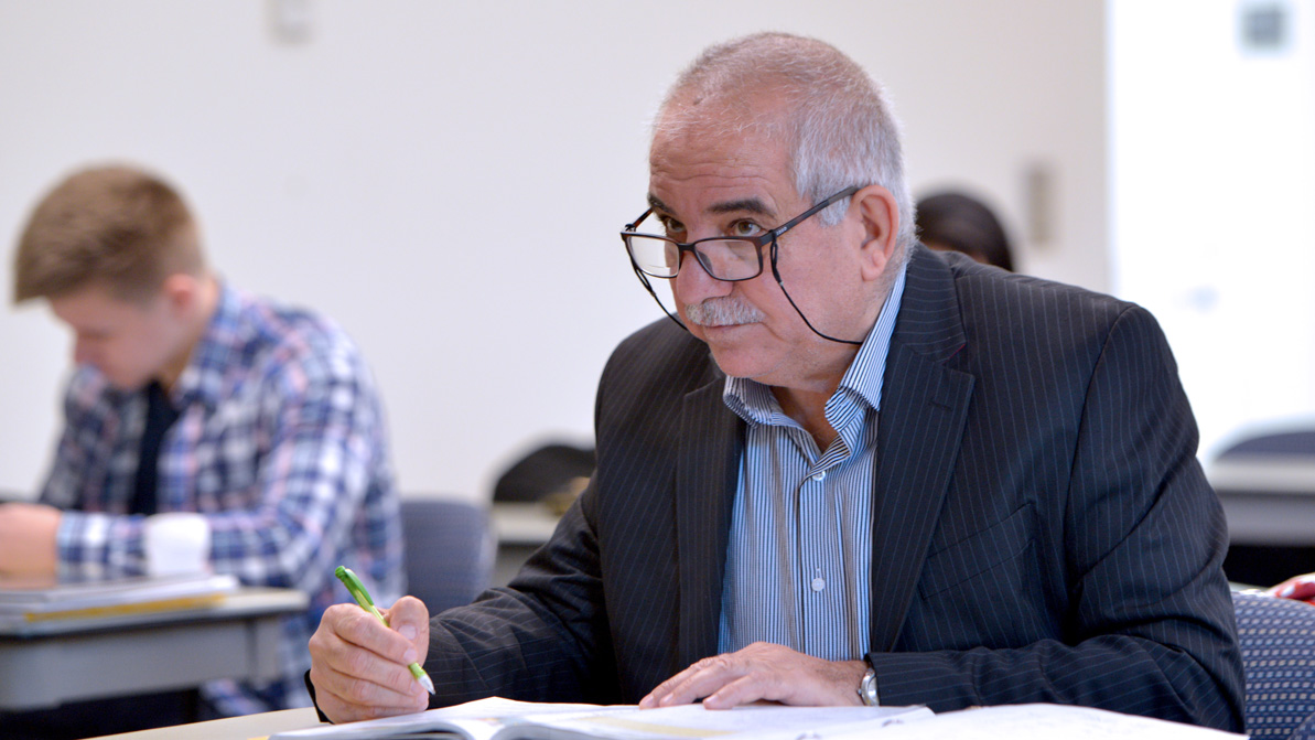 An older male student wearing glasses looks up from his desk