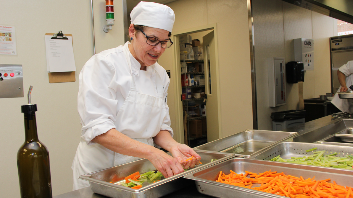 A female adult student works in a culinary environment