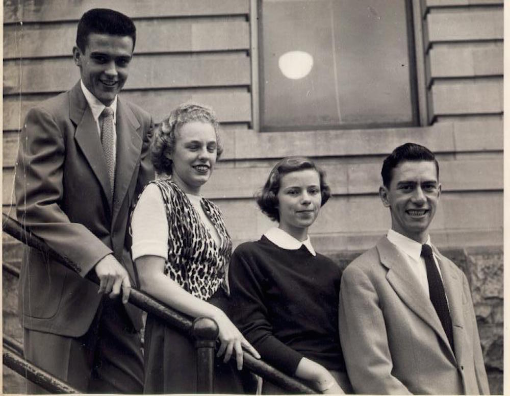 Four people from the class of 1951. Standing from left to right are: William Sullivan, Claire Ducharme, Lucille Brunelle, and Fran Laposta. They are outside but exactly where is not known. Holyoke Junior College.