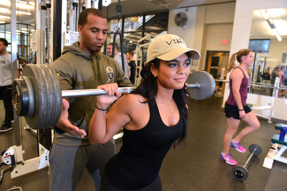 A female student lifts weights while a personal trainer looks on