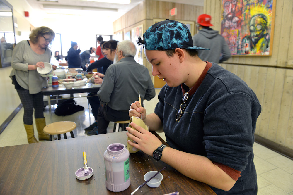 A student painting a clay bowl