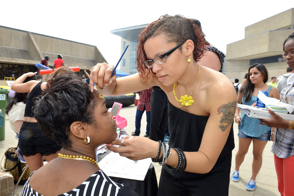 One female student painting another's face during an HCC event