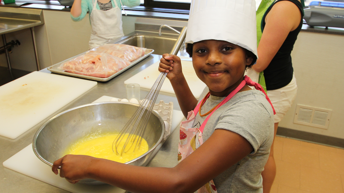 A child using a whisk in the culinary kitchens
